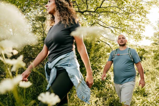 Caucasian couple walking in the park. Young woman and overweight man walking through the woods. stock photo