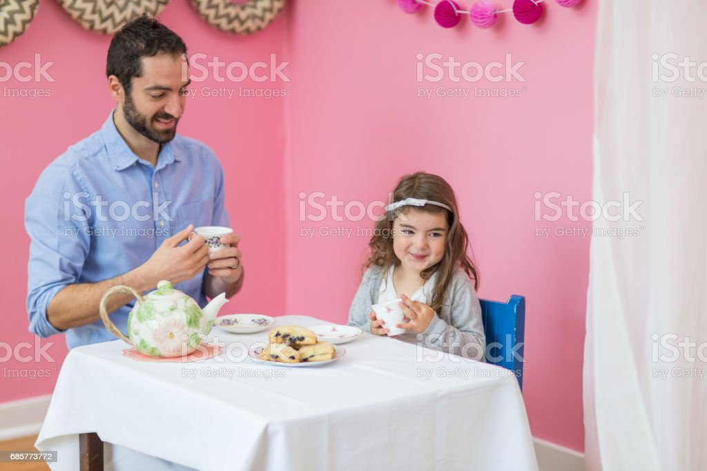 Caucasian dad having a tea party with his young daughter royalty-free stock photo