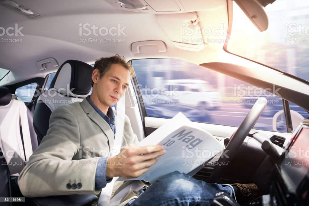 Caucasian driver reading magazine in autonomous car. Self driving vehicle. Driverless car. stock photo