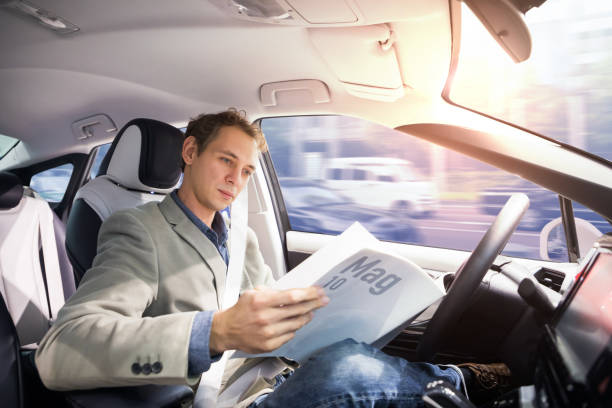 caucasian driver reading magazine in autonomous car. self driving vehicle. driverless car. - self driving car stock photos and pictures
