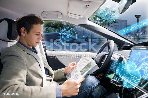 913581100 istock photo Caucasian driver reading magazine in autonomous car. Self driving vehicle. 864461994