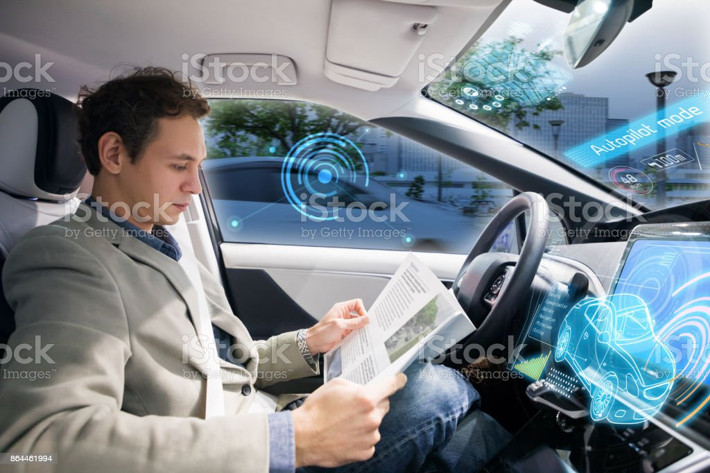 Kaukasiska föraren läser tidningen i autonoma bil. Självkörande fordon. bildbanksfoto