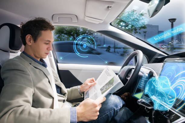 Caucasian driver reading magazine in autonomous car. Self driving vehicle. stock photo
