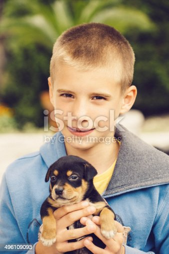 Cute 8 yr old boy with black puppy