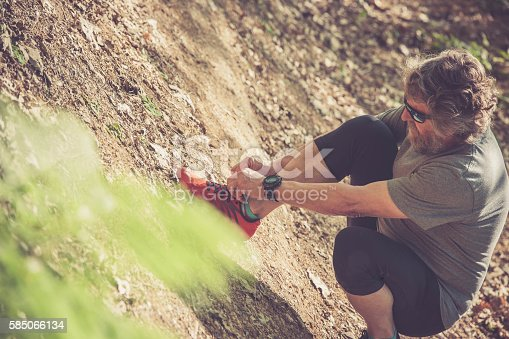 636248376 istock photo Caucasian elderly man with beard and sunglasses lacing sneakers 585066134