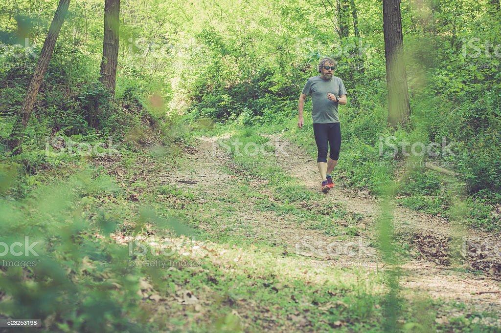 Caucasian elderly man with beard and sunglasses running downhill stock photo
