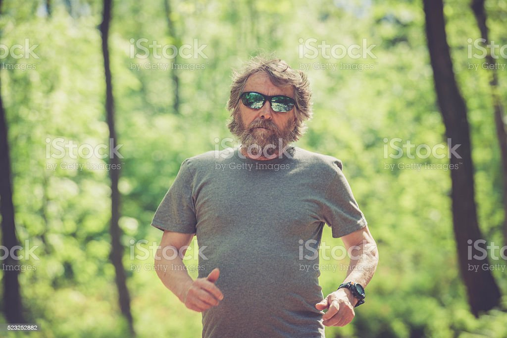 Caucasian elderly man with beard and sunglasses running in forest stock photo