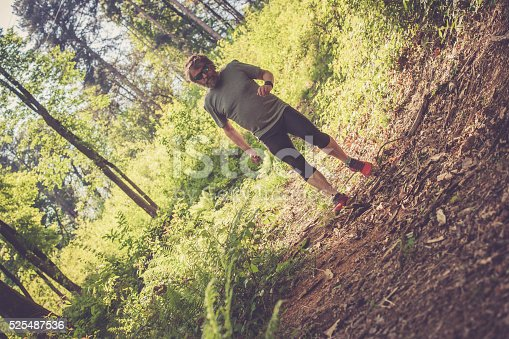 636248376 istock photo Caucasian elderly man with beard and sunglasses running in forest 525487536