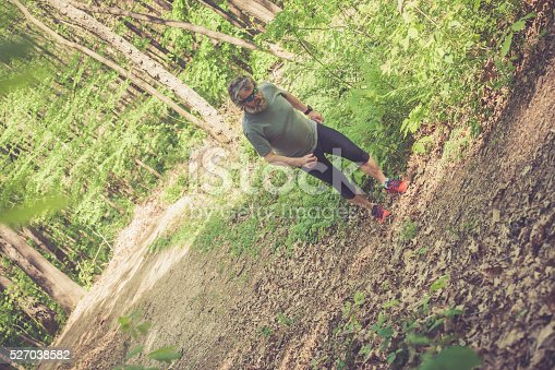 636248376 istock photo Caucasian elderly man with beard and sunglasses running in forest 527038582