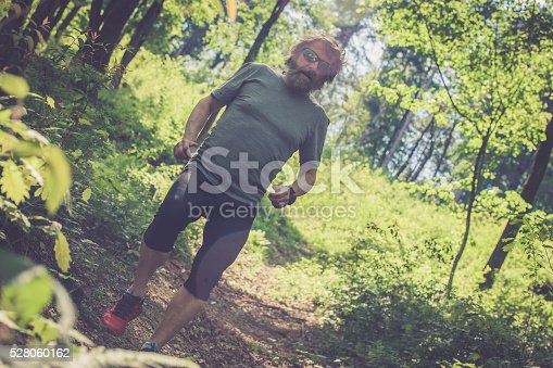 636248376 istock photo Caucasian elderly man with beard and sunglasses running in forest 528060162