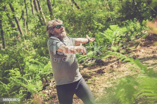 636248376 istock photo Caucasian elderly man with beard and sunglasses stretching outdoors 585063870