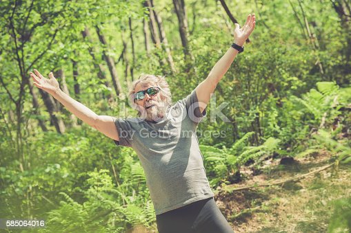 636248376 istock photo Caucasian elderly man with beard and sunglasses stretching outdoors 585064016