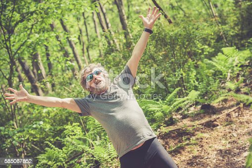 636248376 istock photo Caucasian elderly man with beard and sunglasses stretching outdoors 585067852