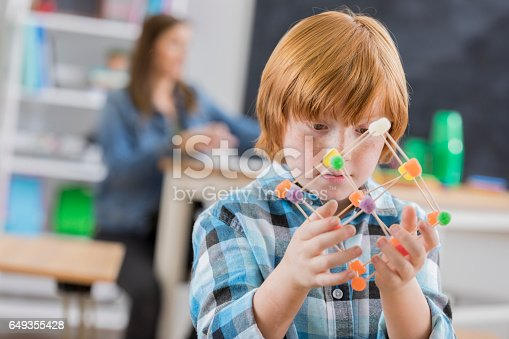 648947070 istock photo Caucasian elementary school student concentrates on engineering project 649355428