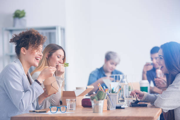 Caucasian employees eating lunch stock photo