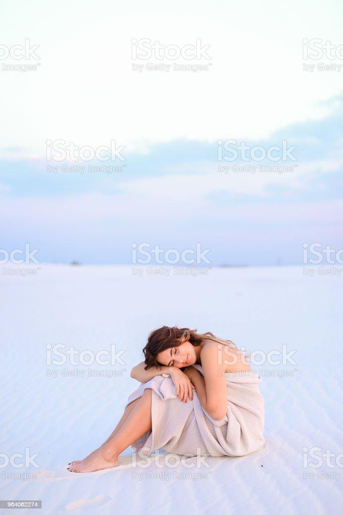 砂の上に座って白い毛布に包まれたヨーロッパの白人の女の子 - アメリカ合衆国のロイヤリティフリーストックフォト