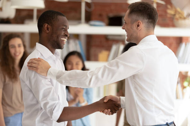 Caucasian executive handshaking promoting successful happy african worker expressing gratitude Caucasian executive boss handshaking promoting successful happy african black worker expressing gratitude praising shaking hand appreciating for good work, reward recognition acknowledgement concept encouragement stock pictures, royalty-free photos & images
