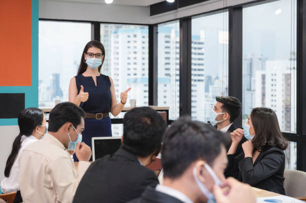 Caucasian executive woman showing thumbs up with proposes company policy on wearing face mask in company during meeting stock photo