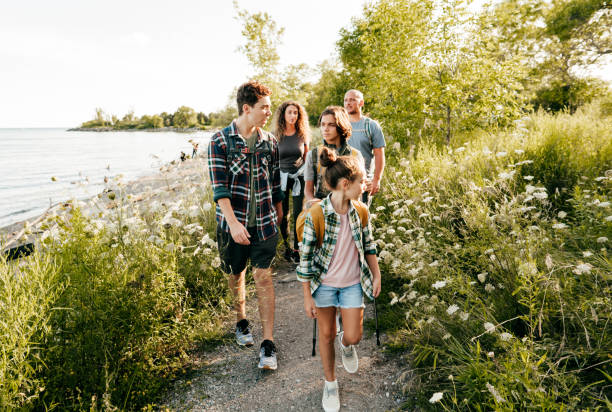 Caucasian family go walking at a lake with three children. Siblings in front of mom and dad walking and talking. stock photo