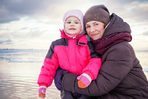Caucasian family outdoor portrait on the winter sea coast, young