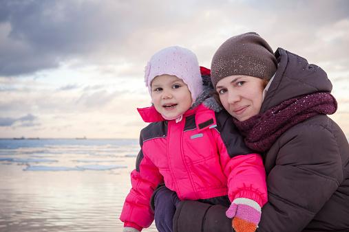 Caucasian family outdoor portrait on winter sea coast, young mot