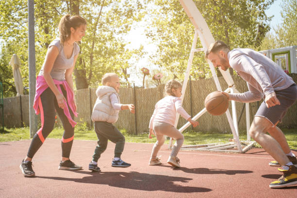 Caucasian family playing basketball together. Happy family spending free time together. stock photo
