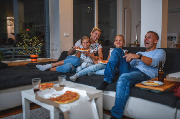 Caucasian Family Sitting on a Sofa Eating Pizza and Watching TV stock photo