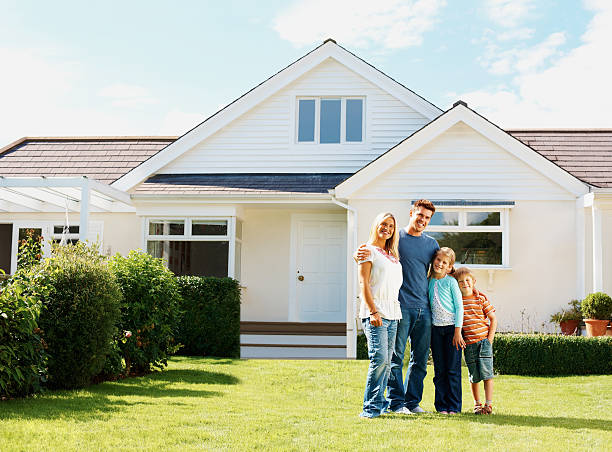 Caucasian family standing in front of a luxury house stock photo