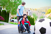 istock Caucasian father helping disabled son in wheelchair play soccer 527271701