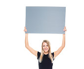 Waist up of aged 20-29 years old who is beautiful with long hair caucasian female businesswoman standing in front of white background wearing businesswear who is cheerful who is showing with hand and holding banner sign with copy space