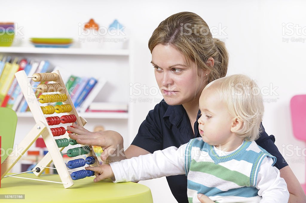 Caucasian Female Carer And Baby/ Toddler Using Counting Frame royalty-free stock photo