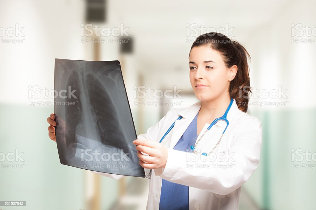 Caucasian female doctor looking at a radiography stock photo