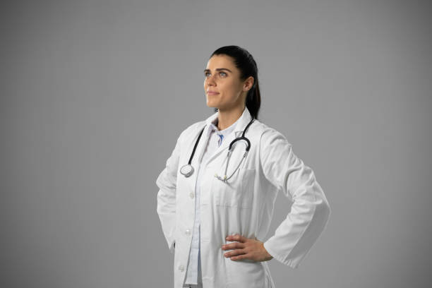 Caucasian female doctor on grey background stock photo