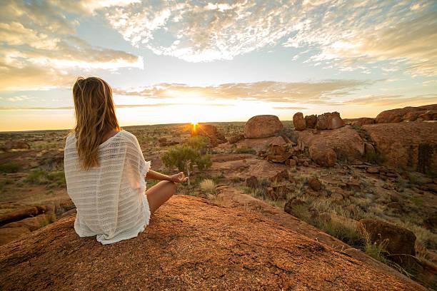 Caucasian female exercising yoga at sunrise stock photo