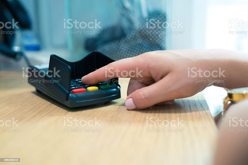 A Caucasian female hand entering a PIN number stock photo