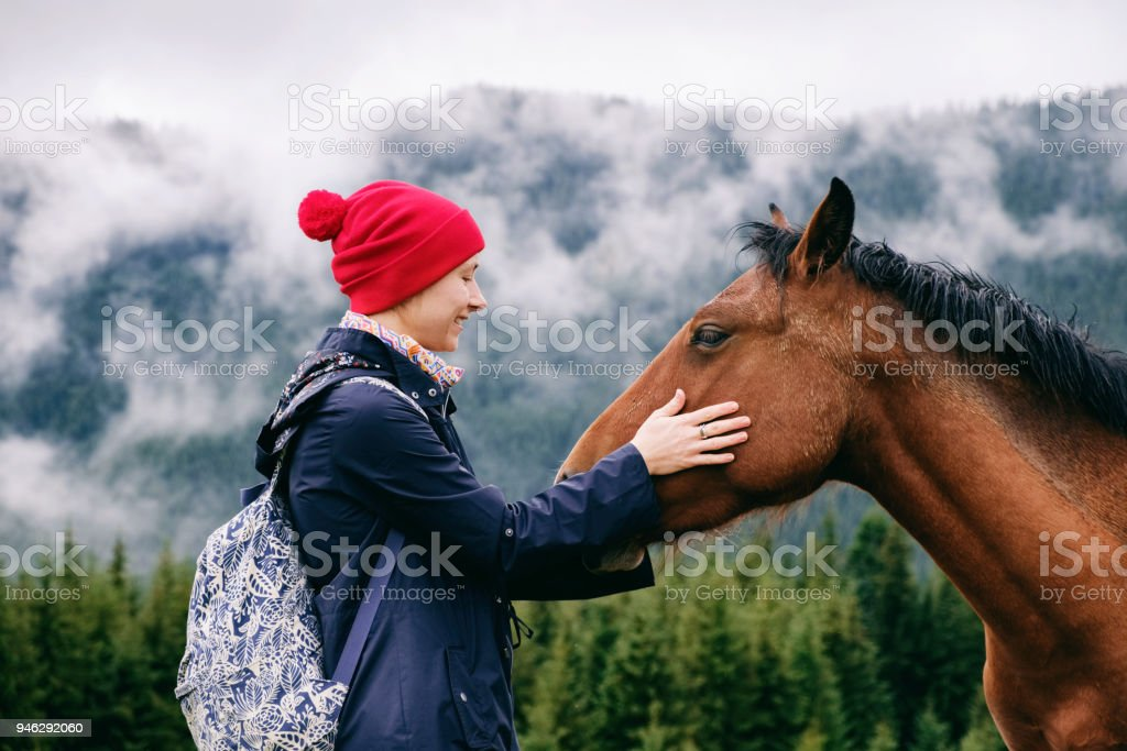 Caucasian female hiker bonding with horse in mountain valley stock photo