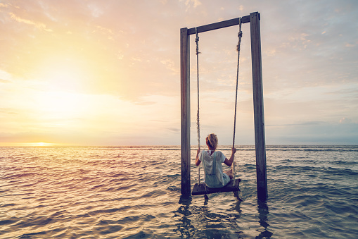 Young woman swinging over the sea at sunset, beautiful and idyllic landscape. People travel vacations concept.
