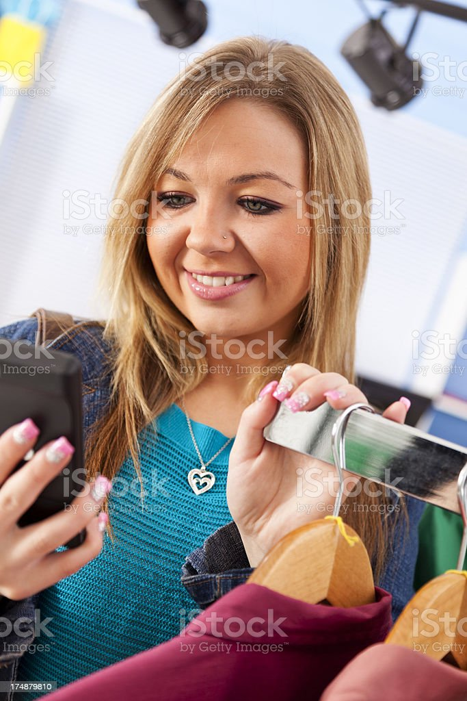 Caucasian female shopper on cell phone while browsing through clothing royalty-free stock photo
