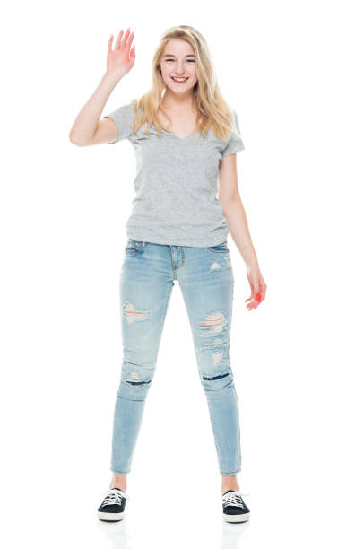 Caucasian female standing in front of white background wearing canvas shoe stock photo