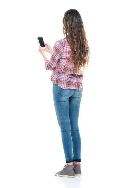 Caucasian female standing in front of white background wearing jeans and using mobile phone stock photo