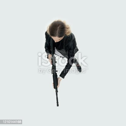 Aerial view of aged 20-29 years old who is beautiful with blond hair caucasian female standing in front of white background wearing pants who is agressive who is shooting a weapon and holding weapon and using machine gun
