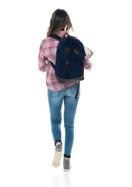 Caucasian female student walking in front of white background wearing backpack and holding book stock photo