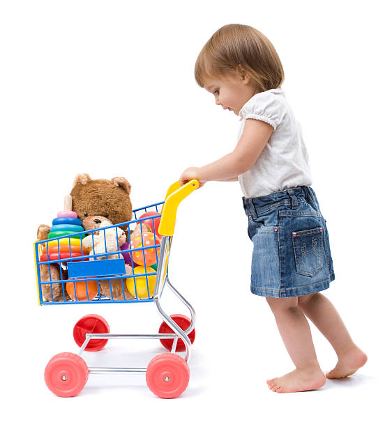 Caucasian Female Toddler with toy shopping cart on white stock photo