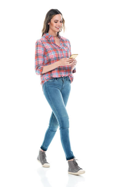 Caucasian female walking in front of white background wearing button down shirt and using smart phone stock photo