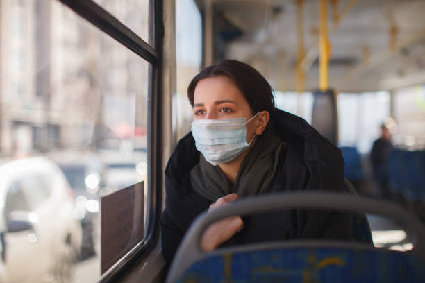 caucasian female with medical mask in urban transport - detachment stock pictures, royalty-free photos & images