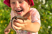 Girl 5 years old, Caucasian, blonde in a red panama. Joyful emotions on his face, laughing cheerfully and holding a caught lizard. The lizard fell into the pool and the girl saved her. Portrait. Summer sunny day. Photos from iPhone 8+