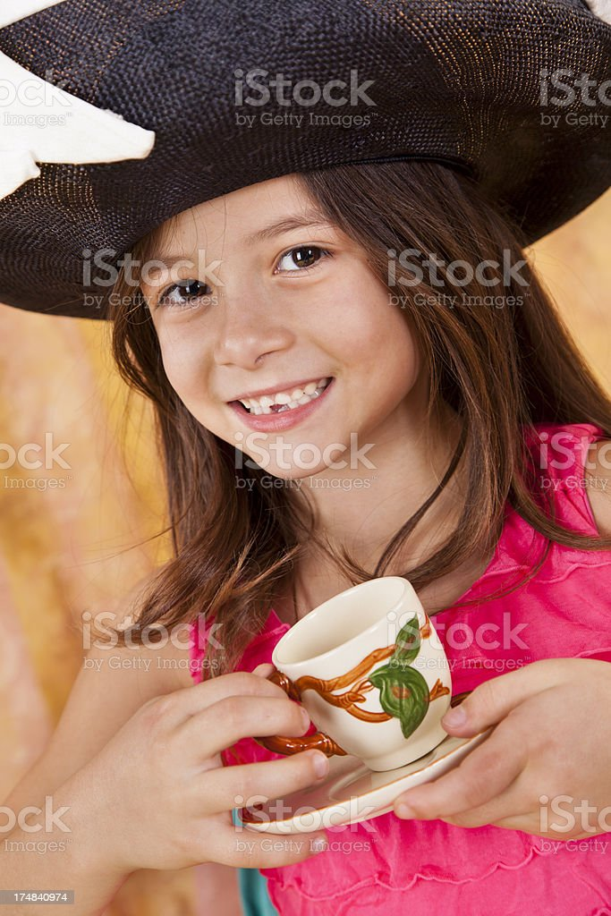 Caucasian girl 7-8, big smile playing tea party with hat royalty-free stock photo
