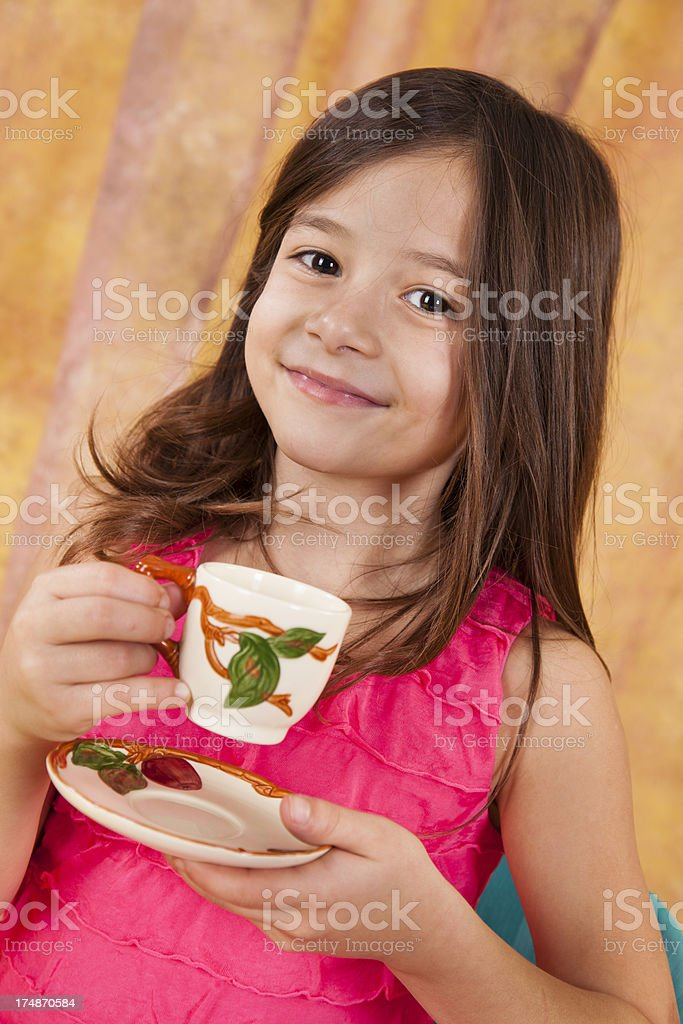 Caucasian girl 7-8, playing tea party holding teacup royalty-free stock photo