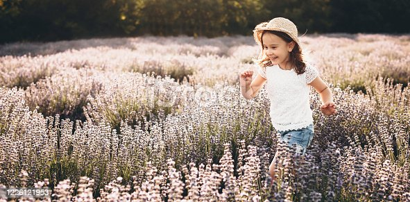 Caucasian girl cheering and running through a lavender field during a sunny summer day