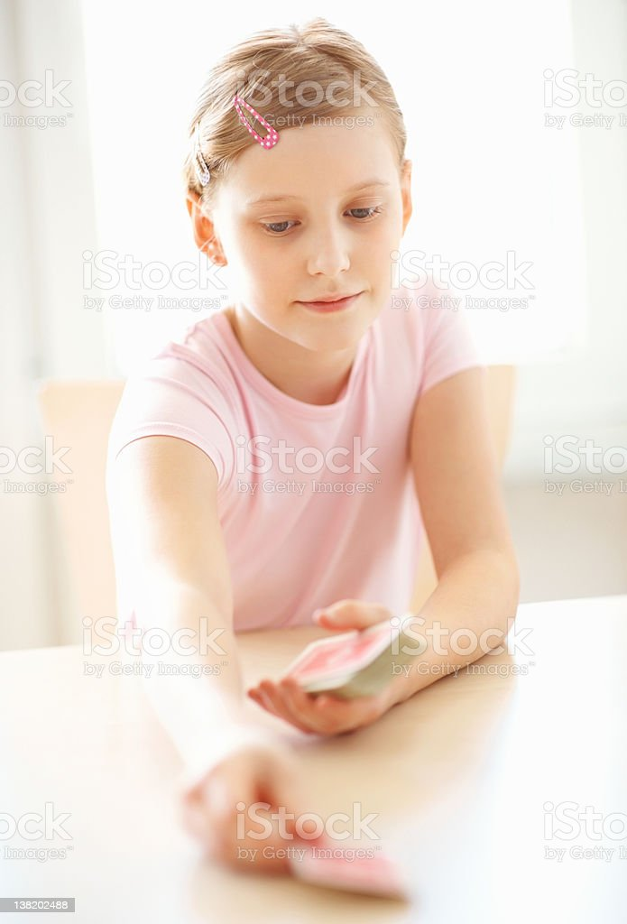 Caucasian girl dealing a deck of cards at the table royalty-free stock photo